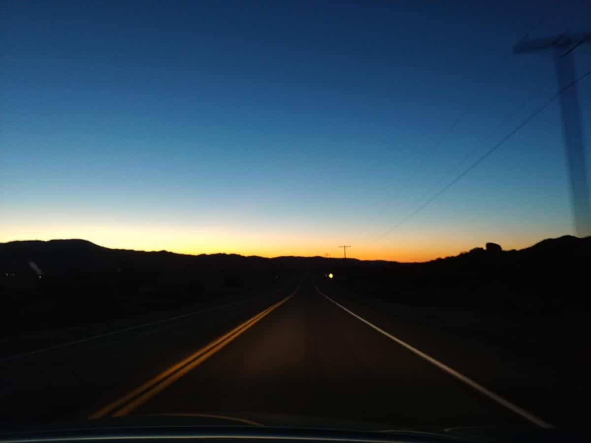 Driving towards the sunset, a line of yellow under a deep deep blue sky