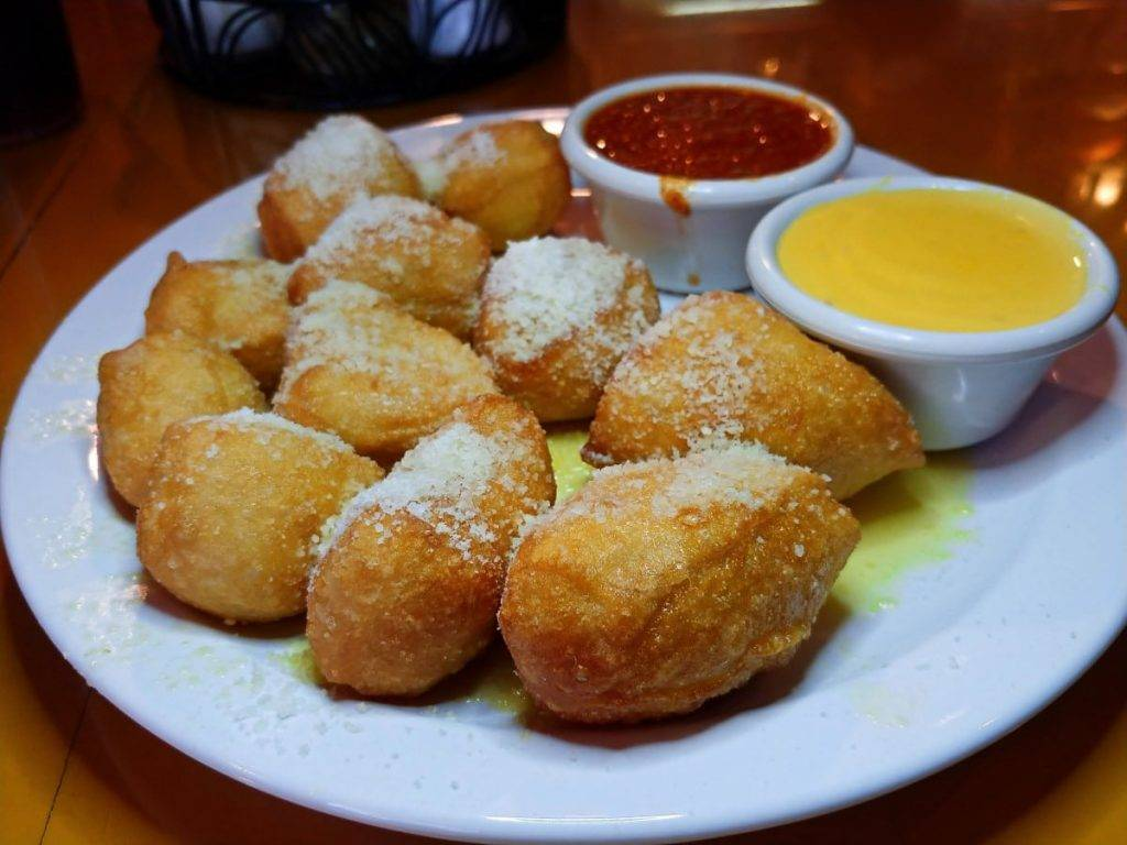 Bruno Dough, deep fried pizza dough topped with butter and parmesan and served with marinara and cheese sauce.