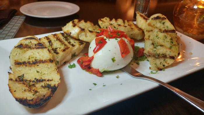 housemade burrata accompanied by roasted red peppers, pesto, and grilled crostini at Fireside Grille in Wichita