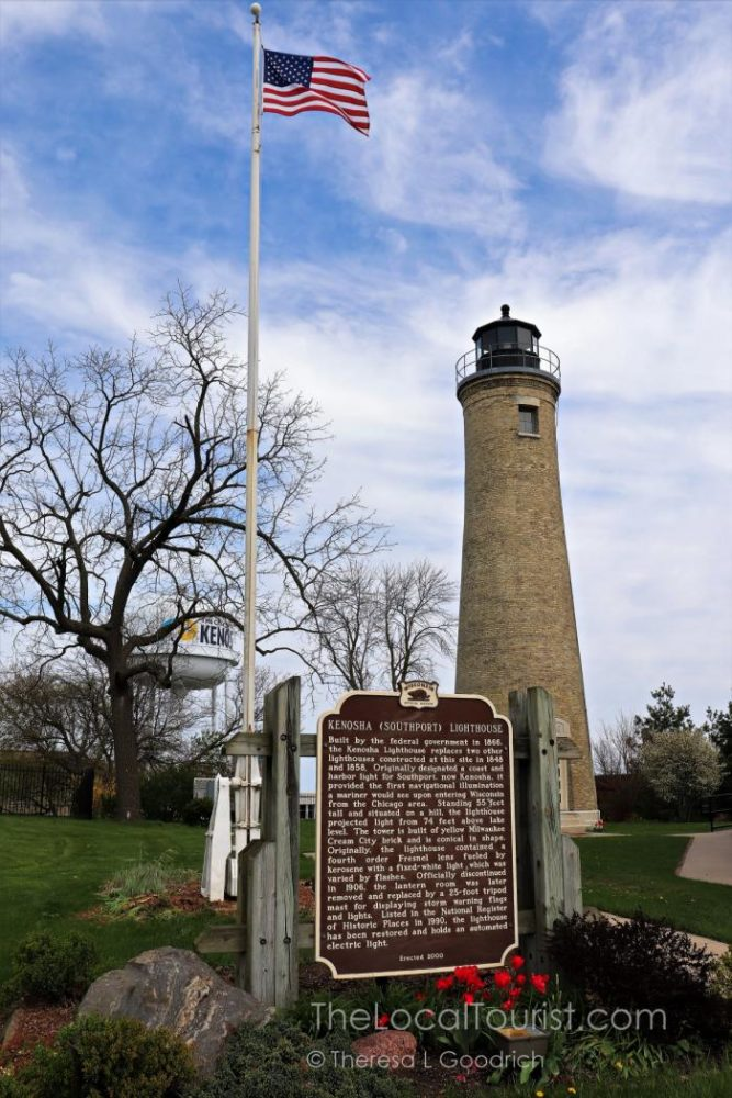 Southport Lighthouse with the Kenosha water tower in the background and an American flag